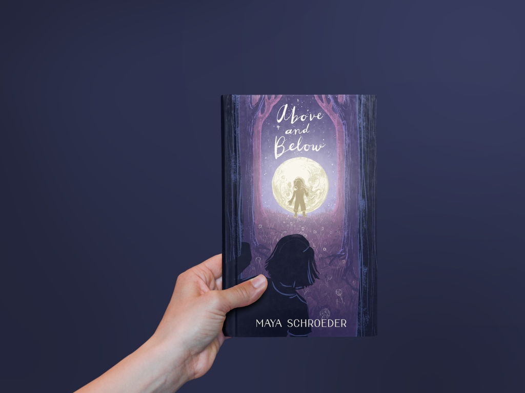 A hand holding an illustrated hardcover book in front of a purple background.
